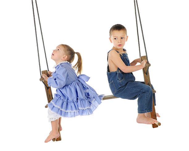 Think It'll Hold? A preschool brother and sister playing on an old wooden, antique 2-person, pump swing together.  The girl is looking up to the top of the ropes, while the brother looks back a bit worried.  On a white background. little girls in panties stock pictures, royalty-free photos & images