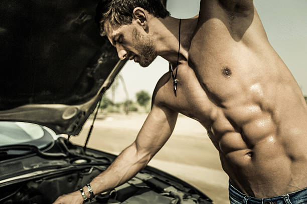 I think my car needs an oil change. Muscular man tending to his car at an outdoor location without his shirt on, displaying his well defined body. shirtless male models stock pictures, royalty-free photos & images