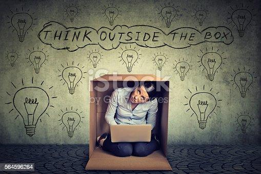 istock Think outside box. Woman sitting inside box 564596264