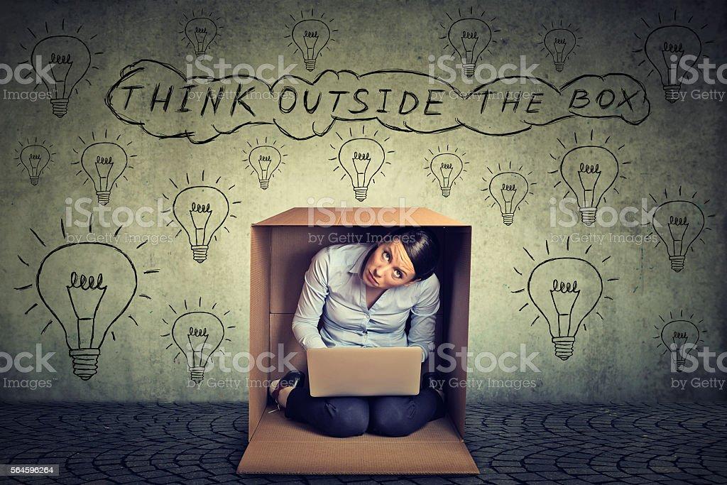 Think outside box. Woman sitting inside box stock photo
