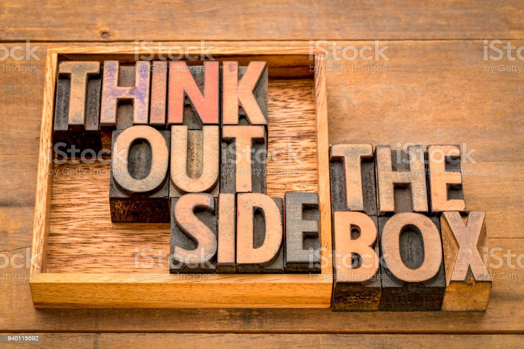think outside the box concept in wood type stock photo