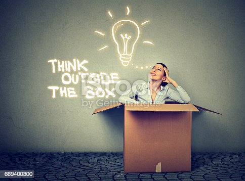 istock Think outside the box concept. Young woman coming out of box with great bright idea light bulb 669400300