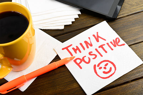 Think positive writing on white napkin Think positive writing on white napkin around coffee pen and phone on wooden table positive emotion stock pictures, royalty-free photos & images