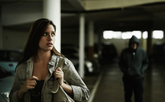 A terrified young woman in an underground parking garage being followed by a sinister man