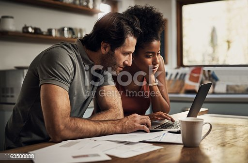Cropped shot of an affectionate young couple using a laptop while doing their budget paperwork in their kitchen at home