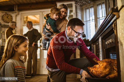 Young happy man taking out baked Thanksgiving turkey from the oven for his family's lunch in the kitchen.