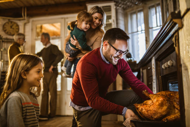 I think this Thanksgiving turkey is baked! Young happy man taking out baked Thanksgiving turkey from the oven for his family's lunch in the kitchen. oven stock pictures, royalty-free photos & images