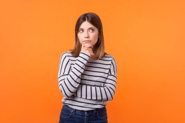 Think up plan. Portrait of pensive woman with brown hair in long sleeve striped shirt. indoor studio shot isolated on orange background stock photo