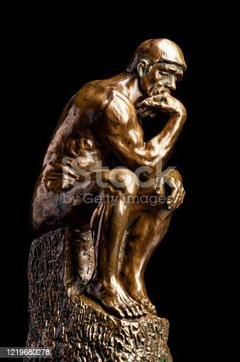 A bronze replica statue of Rodin's Thinker on black