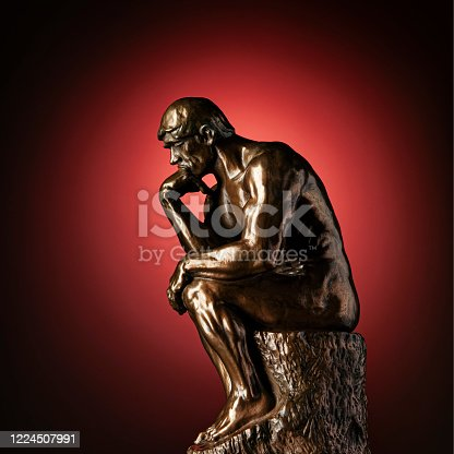 A bronze replica statue of Rodin's Thinker on a red background with vignette