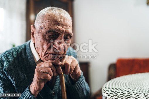 Older man with walking stick, leaning his head on it. Sitting and thinking about life.