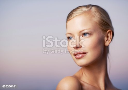 A beautiful young model glancing over her shoulder against a soft purple background