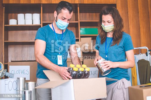 Volunteers working in charitable foundation Warehouse on helping homeless people.Social workers who provide humanitarian assistance to a disadvantaged person