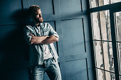 Handsome young bearded man in light jeans shirt keeping arms crossed and looking away while standing near the window
