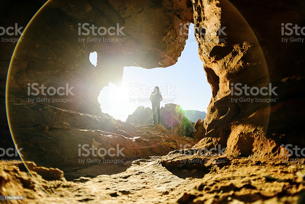 Thinking about the future Female looking into the sun between rocks Active Lifestyle Stock Photo