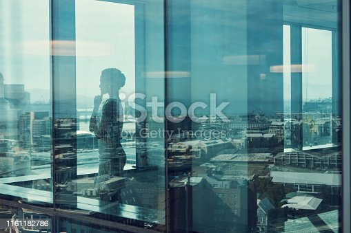 Shot of a businesswoman standing inside a glass building with a reflection of the city in the background