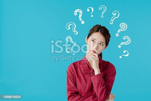 istock Thinking asian woman. 1068618334