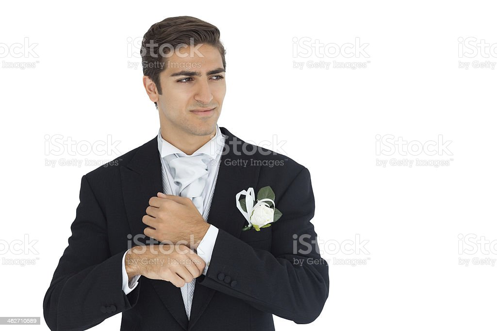 Thinking attractive young groom buttoning his cufflinks stock photo