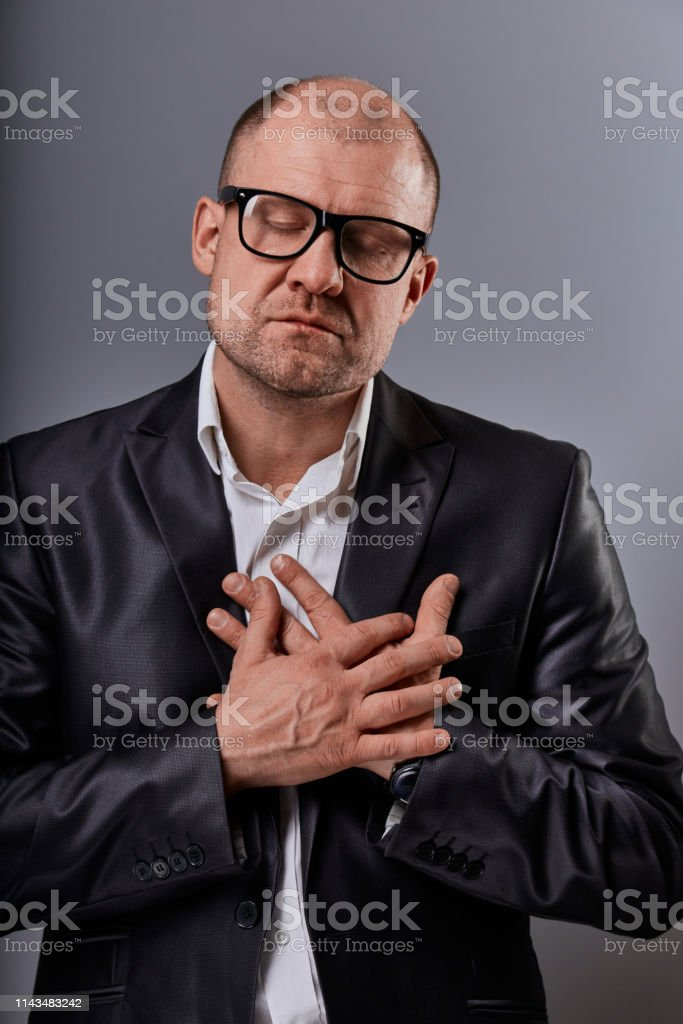 Thinking bald business man holding the chest two hands with serious face and closed eyes in eyeglasses in suit on grey background. Closeup royalty-free stock photo