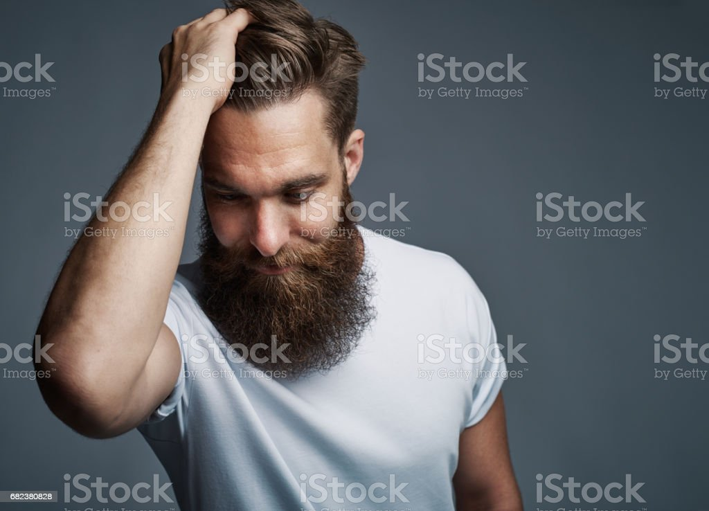 Thinking bearded man holding hair and laughing royalty-free stock photo