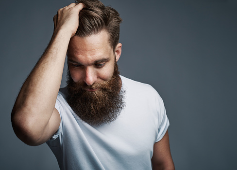 Thinking Bearded Man Holding Hair And Laughing Stock Photo - Download Image Now