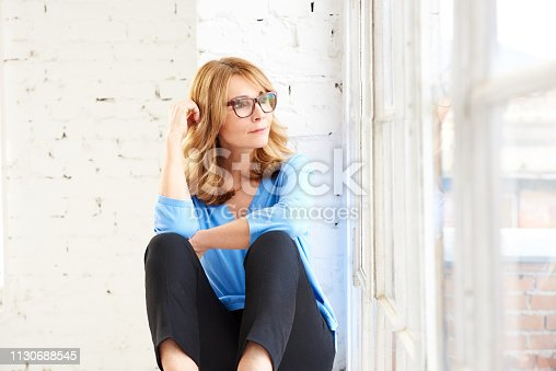 Portrait shot of middle aged woman sitting at the window and looking out while daydreaming.