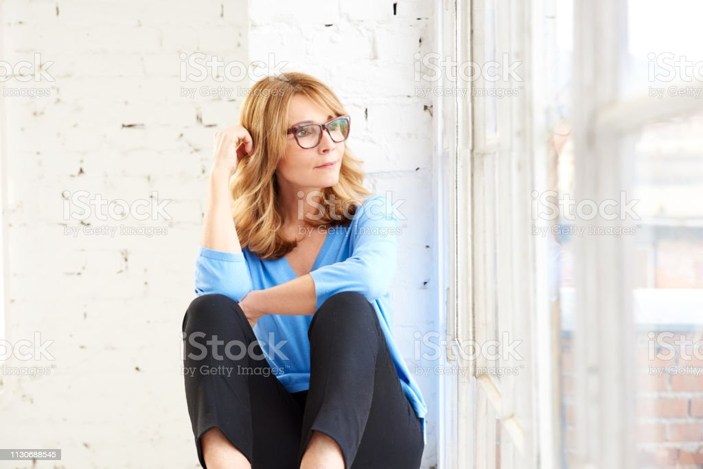 Thinking beautiful lady looking out the window while sitting and realxing стоковое фото