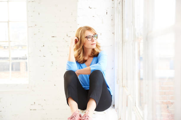 Denken Sie schöne Dame aus dem Fenster, während sitzen und neu – Foto