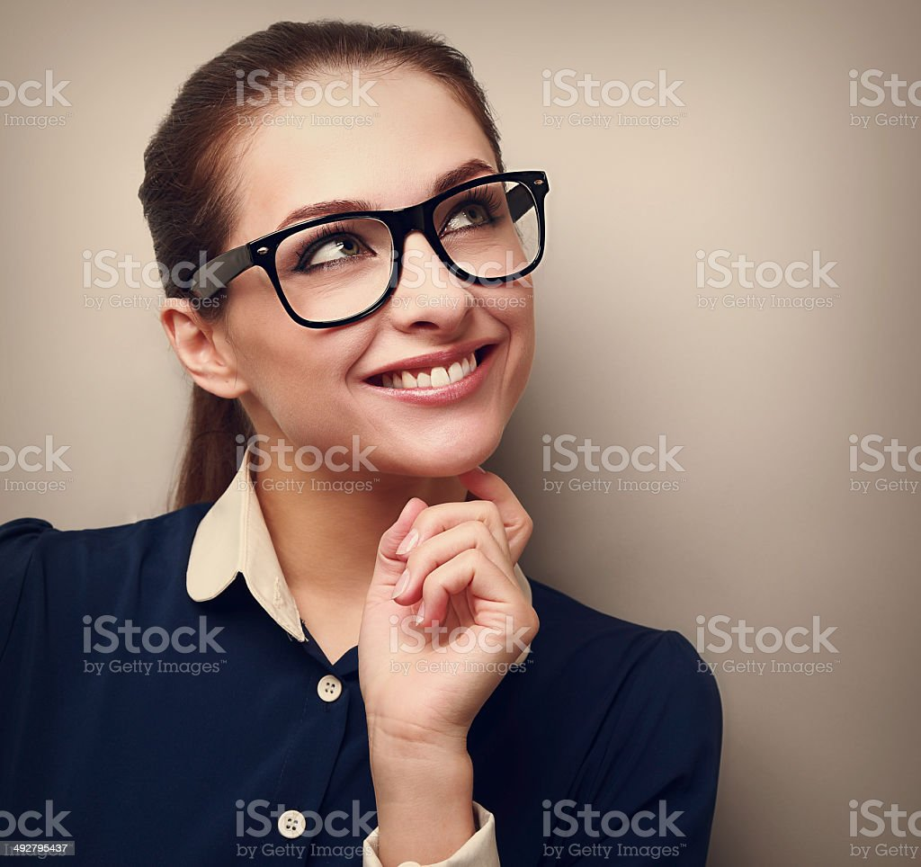 Thinking business woman looking up with hand at face. Vintage stock photo