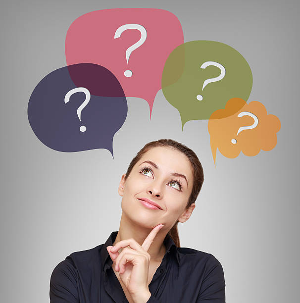 Thinking business woman with many questions in bubbles above stock photo