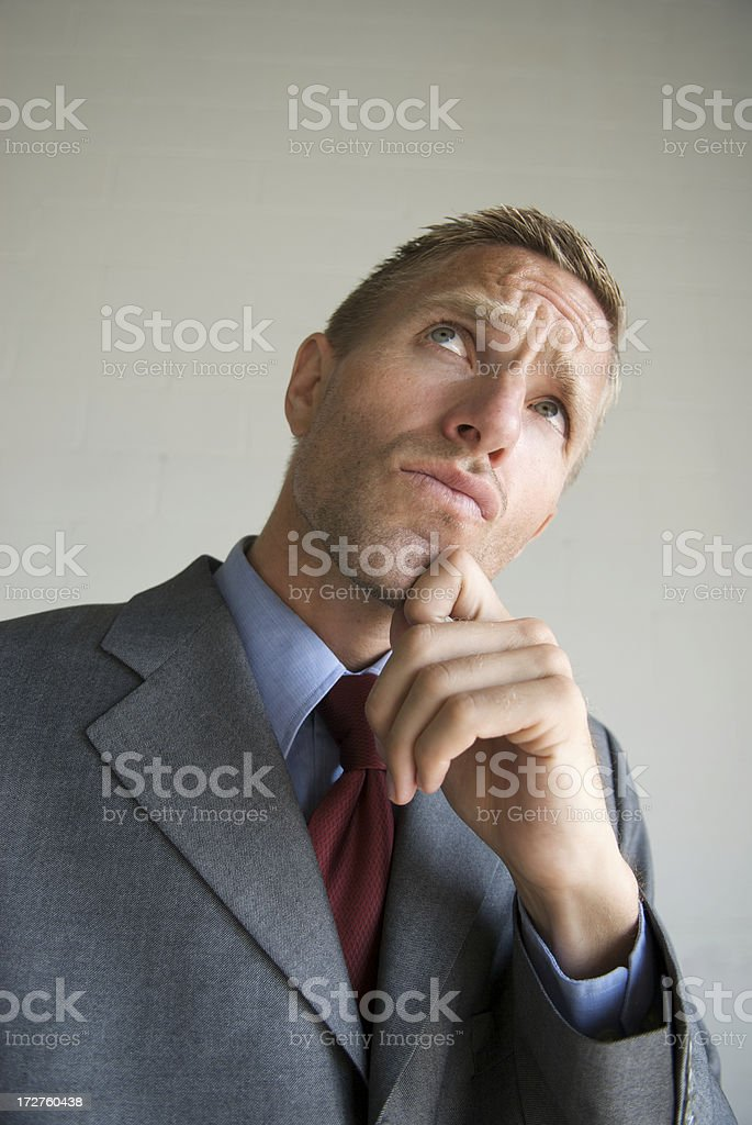 Thinking Businessman Looking Up with Hand on Chin royalty-free stock photo