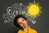 istock Thinking child boy on black background with light bulb and question marks. Brainstorming and idea concept 1252494221