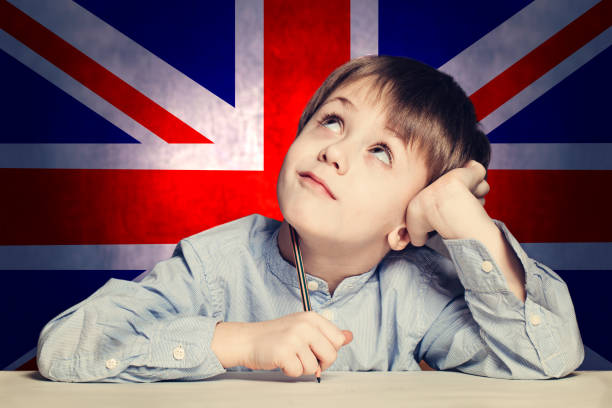 Thinking child boy student look up on the UK flag background. English concept Thinking child boy student look up on the UK flag background. English concept english language stock pictures, royalty-free photos & images