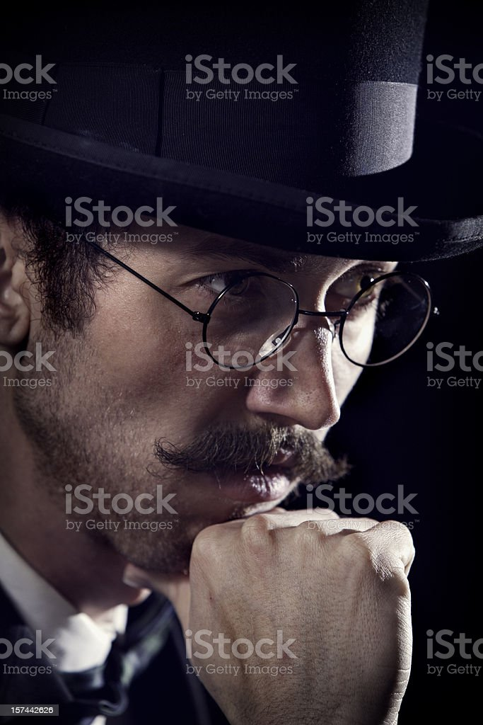 A sophisticated and classy looking man in a top hat and spectacles...