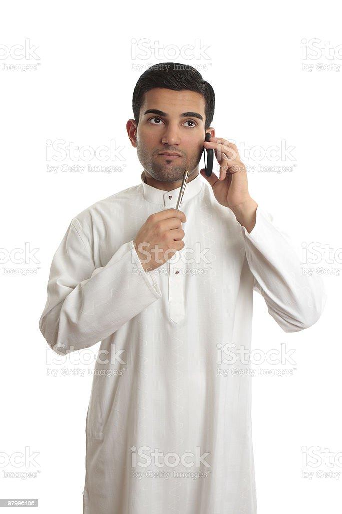 Thinking ethnic businessman on mobile phone royalty free stockfoto