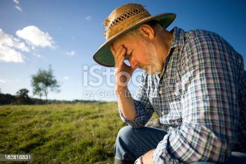 Photograph of a farmer thinking with his head in his hand.