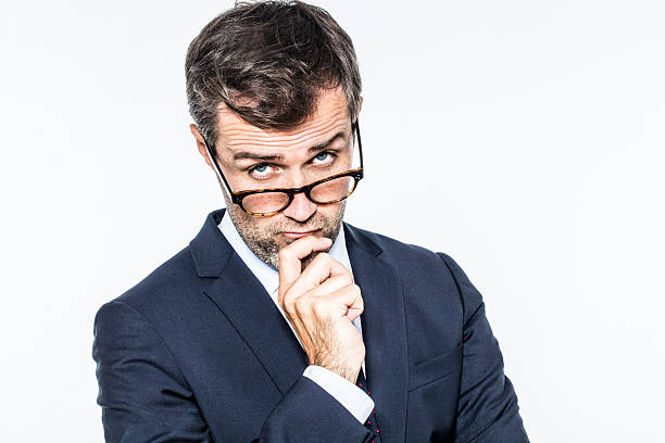 thinking far-sighted middle aged businessman with eyeglasses down thinking far-sighted middle aged businessman with eyeglasses down for management eye view, looking questioning, white background studio raised eyebrows stock pictures, royalty-free photos & images