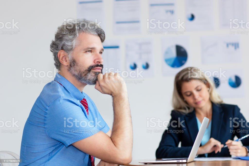 Hombre de negocios alemán de pensamiento con cabello gris y una computadora - foto de stock