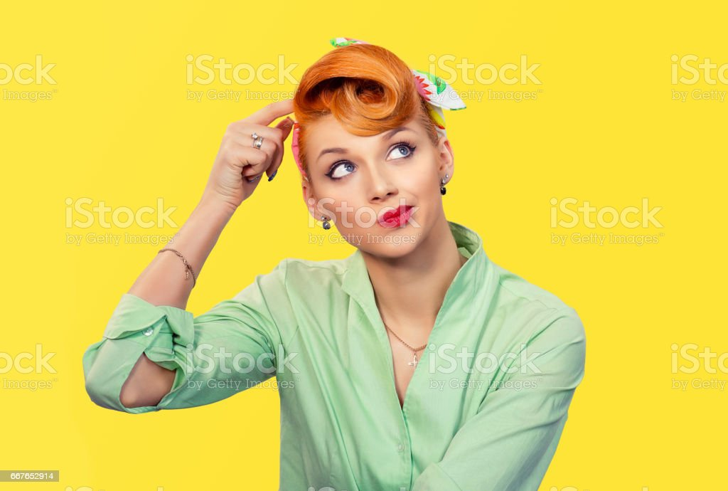 Thinking girl. Portrait closeup funny confused skeptical woman girl female thinking trying to recall looking upwards isolated yellow wall background. Human expressions emotions feelings body language stock photo