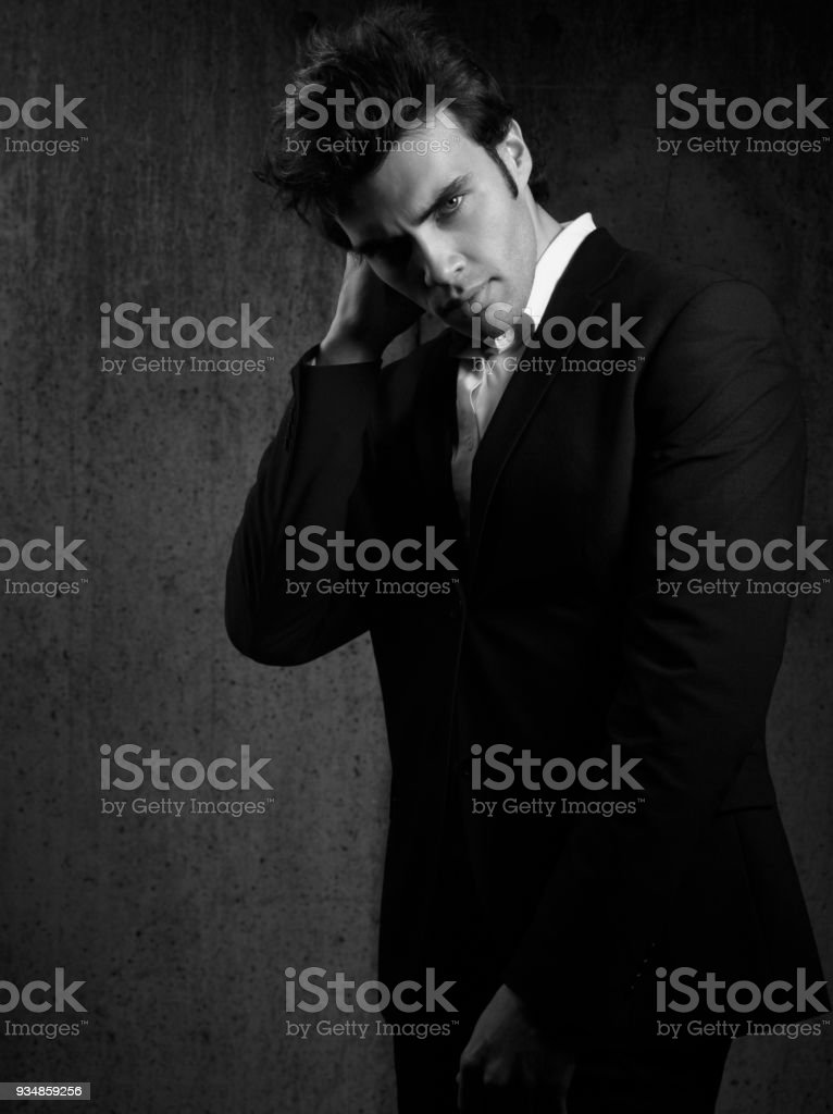 34285a65 Thinking handsome male model posing in blue fashion suit and white style  shirt looking on dark
