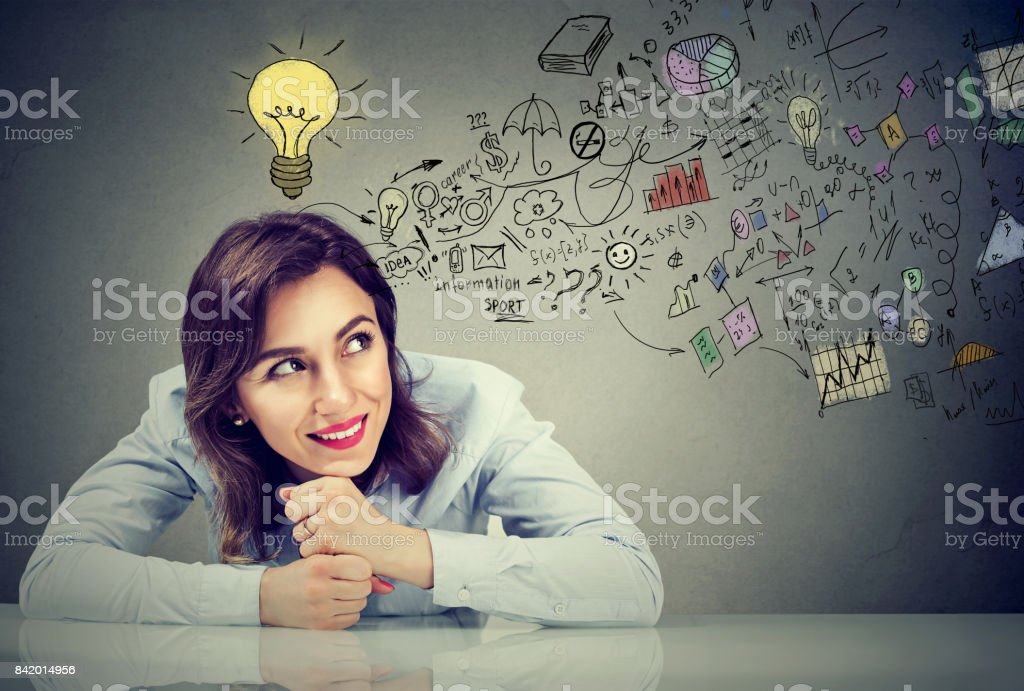 Thinking happy business woman sitting at desk planning stock photo