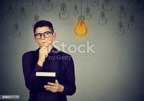 istock Thinking man looking up at light idea bulb above head . 636347770