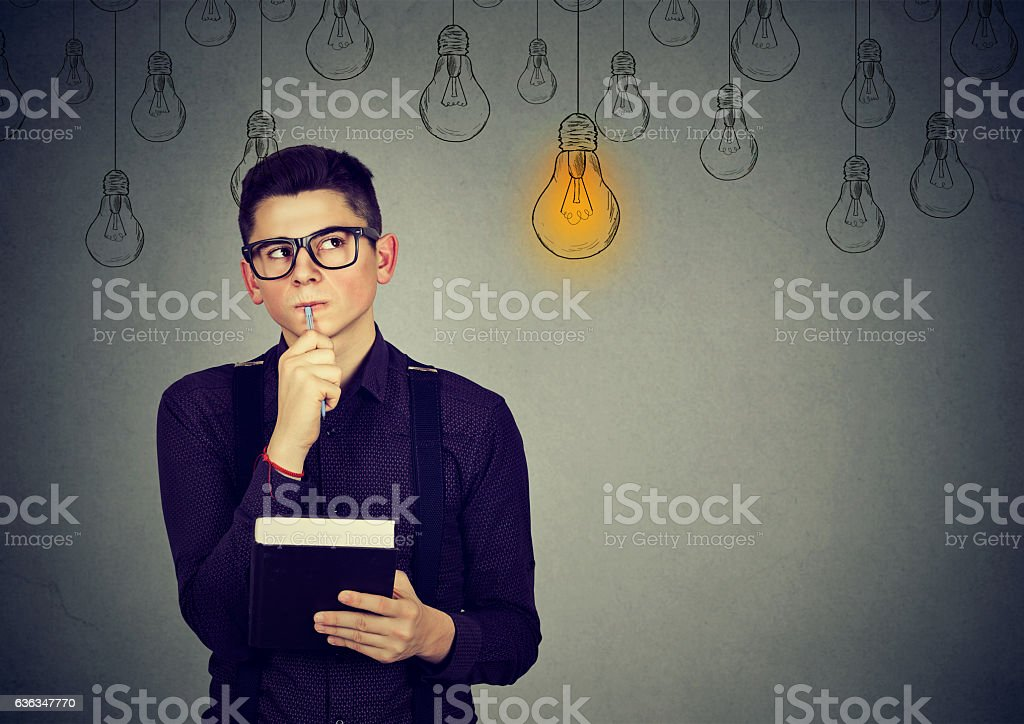 Thinking man looking up at light idea bulb above head . stock photo