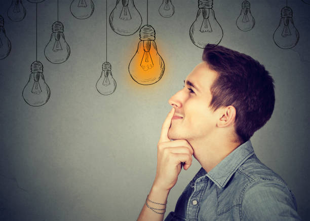 thinking man looking up with light idea bulb above head isolated on gray wall background - genius stock photos and pictures