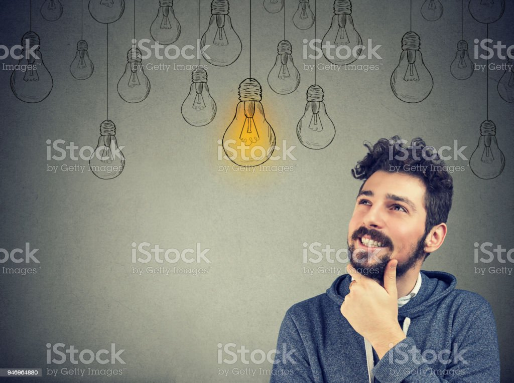 thinking man smiling looking up at light idea bulb above head – zdjęcie