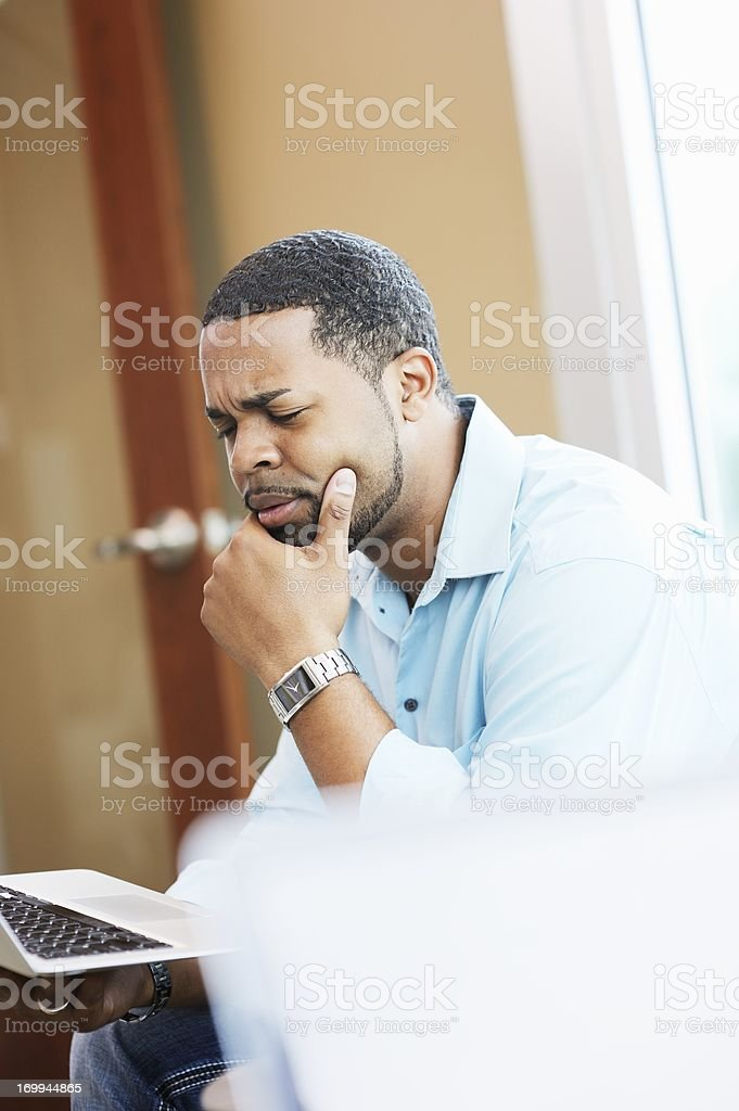 Thinking Man Using Laptop stock photo