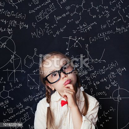 istock Thinking mathematics student on school blackboard background with chalk hand drawings science formula pattern. Kids mathematics education concept. 1019220194