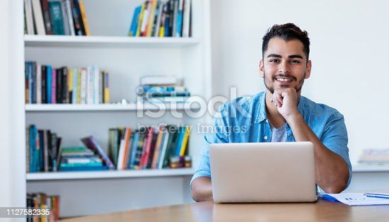 1127582480istockphoto Thinking mexican hipster man working with computer 1127582335