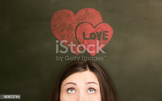 Thinking of love girl in front of two painted hearts on a blackboard.