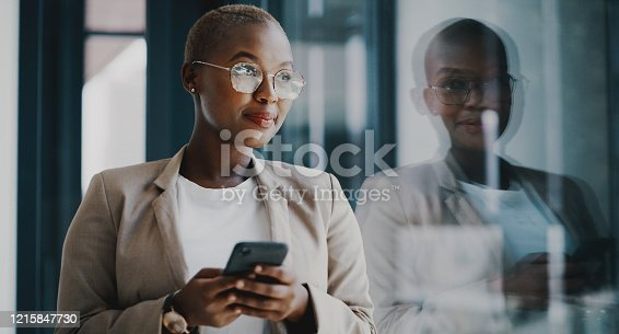 Shot of a young businesswoman using a cellphone while standing at a window in an office